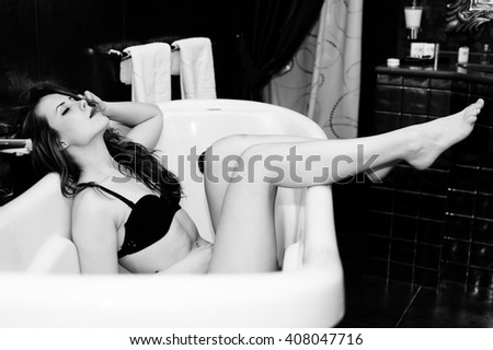 Black and white photography of sexy beautiful young lady having fun in bath tub relaxing eyes closed - stock photo