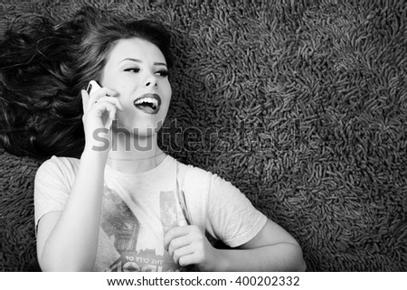 Black and white photography of sexy young beautiful woman relaxing and talking on mobile phone over copy space  - stock photo