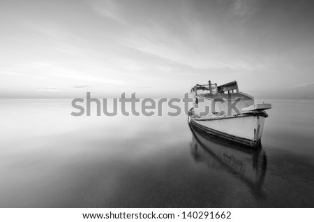 black and white photography of sky and sea at sunrise with a little old boat abandoned in the Mar Menor, Spain - stock photo
