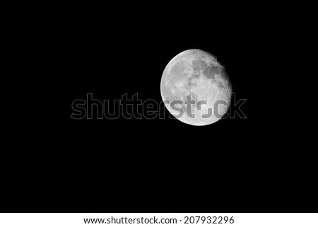 Black and White photography of the Moon almost full seen from the northern hemisphere with a telescope - stock photo