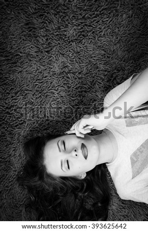 Black and white photography of young beautiful woman talking on mobile phone with eyes closed - stock photo