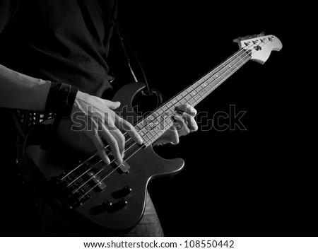 black and white picture of bass guitar in male hands - stock photo