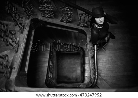 Black and white picture of mysterious woman in hat posing on spiral stairs
