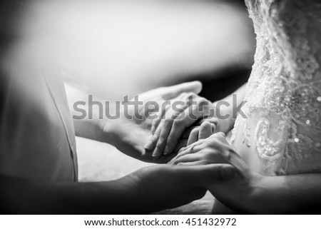 Black and white picture of newlyweds holding their hands together