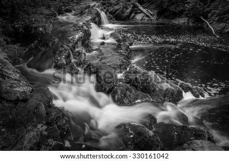 black and white picture of running water in the stones - stock photo