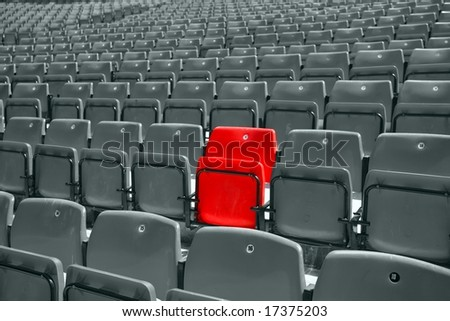 black and white picture of stadium seat with only one red - stock photo