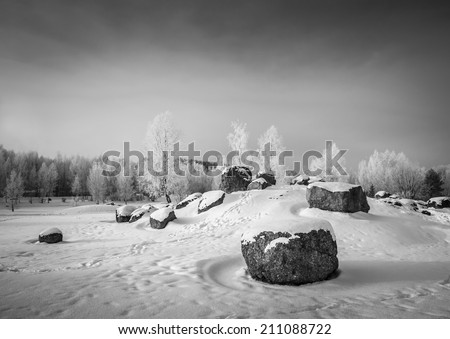 black and white picture of the winter boulder park with snow - stock photo