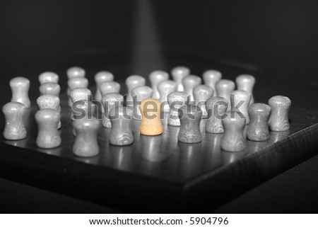 Black and white picture peg of a solitaire game with the central peg colored and lit under a beam. Concept of difference, loneliness. - stock photo