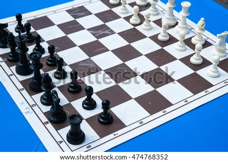 Black and white plastic chess pieces on a cheap and used paper chess board on a blue table. Open air chess competitions.