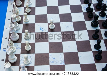 Black and white plastic chess pieces on a cheap paper chess board. White pawn made the first move of a game. Open air chess competitions. Nobody around