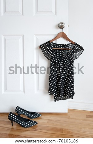 Black and white polka dot shoes and stylish blouse on a hanger. - stock photo