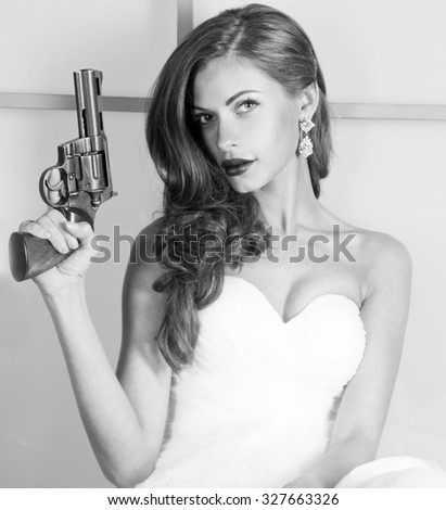 Black and white portrait, beautiful girl in a wedding dress with a gun, studio shooting - stock photo