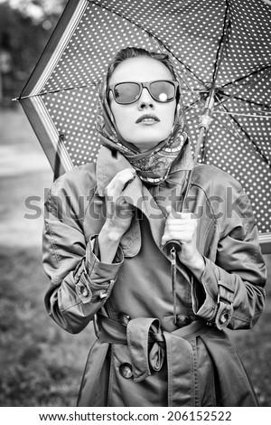 Black and white portrait beautiful girl in the rain with umbrella - stock photo
