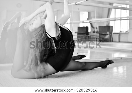 black and white portrait of a beautiful ballerina stretching and doing exercises in ballet hall - stock photo