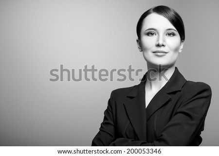 Black and white portrait of a beautiful elegant professional woman standing with folded arms in a stylish jacket looking at the camera with an enigmatic smile, with copy space - stock photo