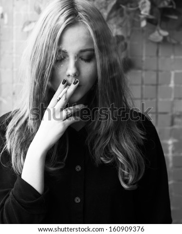 black and white portrait of a beautiful girl smoking - stock photo