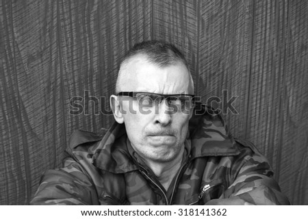 Black and white portrait of a displeased man with a side gaze - stock photo