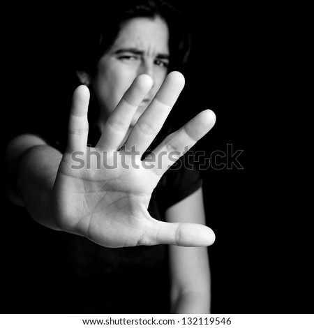 Black and white portrait of a frightened woman extending her hand trying to stop any coming danger on a black background - stock photo