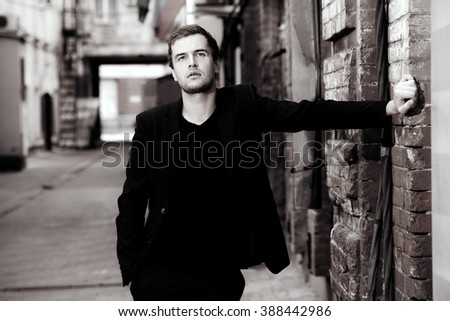 Black-and-white portrait of a handsome elegant man posing on a city street. Fashion shot. Business man outdoor. - stock photo