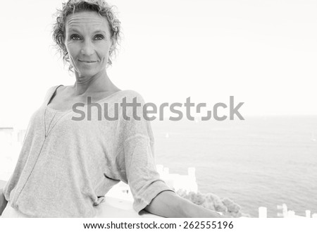Black and white portrait of a middle age attractive woman relaxing in her holiday resort hotel balcony, contemplating the sea during a summer vacation day, outdoors. Beauty and lifestyle well being. - stock photo