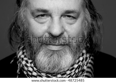 Black-and-white portrait of a smiling old man with beard looking to viewer - stock photo
