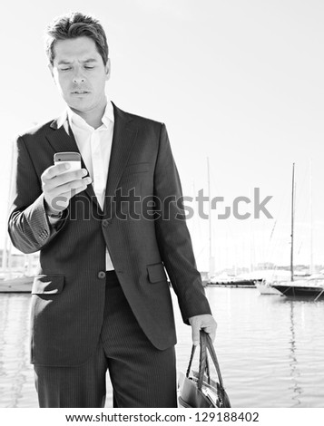 """Black and white portrait of a stylish businessman using his """"smart phone"""" while standing near a marine with luxury yachts. - stock photo"""