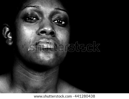 Black and white portrait of a tearful african american woman posing against a black background