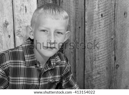 Black and white portrait of a ten year old boy with rustic wood background. - stock photo
