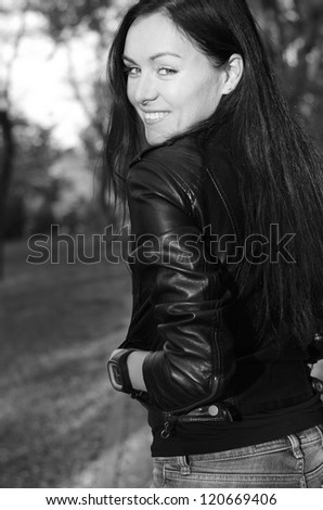 Black and white portrait of a trendy young woman wearing a leather jacket looking back over her shoulder at the camera with a smile - stock photo