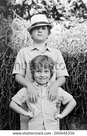 black and white portrait of a two brothers outdoors . - stock photo