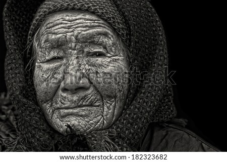 Black and white portrait of a 95 years old woman, born in 1919, with depression, the last generation that bind the feet of woman - stock photo