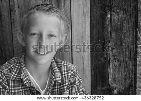 Black and white portrait of a young boy with a rustic wood background. - stock photo