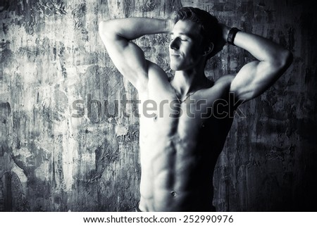 Black-and-white portrait of a young handsome man with beautiful muscular body. Men's beauty, healthcare. - stock photo