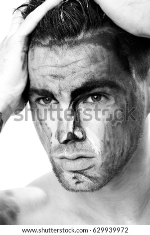 black and white portrait of a young man with streaks of paint on face . fantasy art of makeup