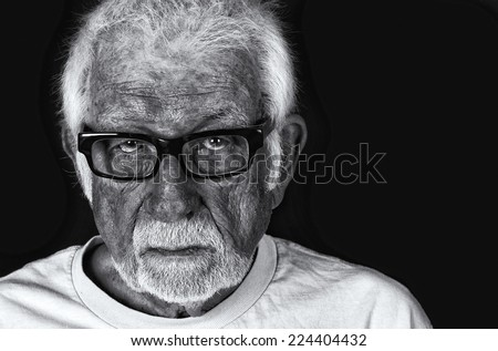 Black and white portrait of an elderly sad man with a tear rolling down his cheek - stock photo