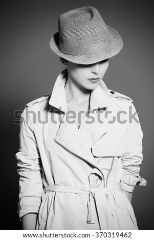 Black-and-white portrait of an elegant fashion model posing at studio in a coat and hat. Beauty, fashion. Business style. - stock photo