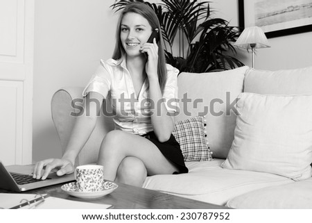 Black and white portrait of an young professional business woman sitting on a white sofa at home making a call on a smartphone, working on laptop computer, drinking a coffee smiling, home interior.