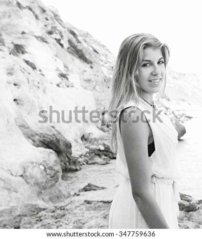 Black and white portrait of beautiful adolescent girl visiting a beach on holiday, contemplating the sea and turning looking smiling at the camera, outdoors vacation. Teenager summer lifestyle. - stock photo