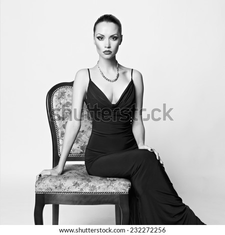 Black and white portrait of beautiful lady in luxury armchair - stock photo