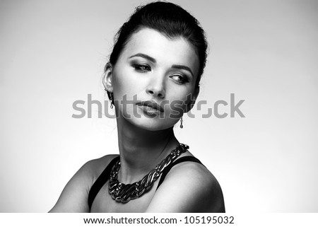 Black and white portrait of beautiful woman  in black dress with jewelry on natural background