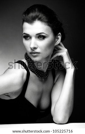 Black and white portrait of beautiful woman  in black dress with pearl necklace