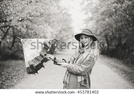 Black and white portrait of beautiful young lady with rainbow umbrella having fun happy smiling and looking at camera over autumn road copy space background - stock photo