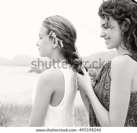 Black and white portrait of beautiful young sisters relaxing together on coastal beach dunes, caring platting hair, embellishing and loving by the sea, smiling outdoors. Health and beauty lifestyle.