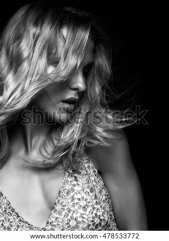 Black and white portrait of beauty young  woman in summer casual dress with shaggy hair on black background