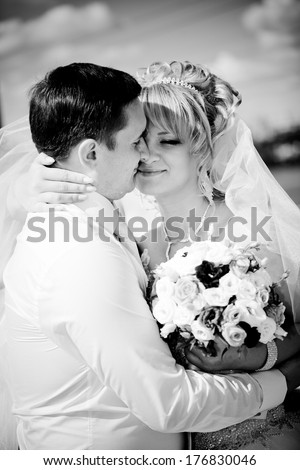 Black and white portrait of bride and groom hugging tenderly outdoor
