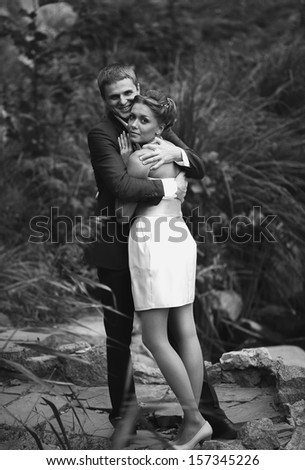 Black and white portrait of bride cuddling to groom