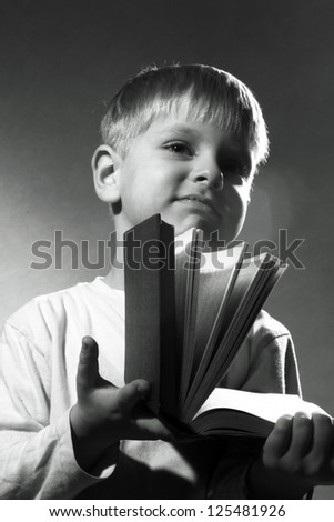black and white portrait of cute little boy closing the book - stock photo