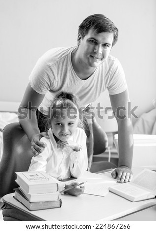 Black and white portrait of daughter doing homework with father at home