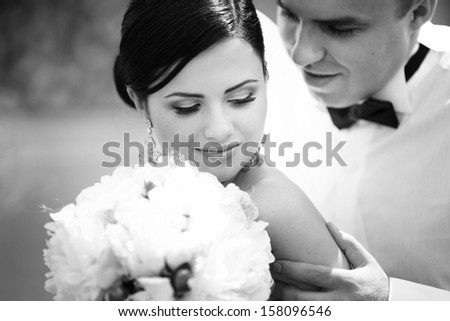Black and white portrait of groom and bride - stock photo