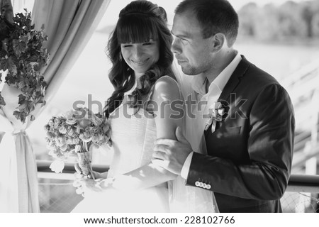 Black and white portrait of groom hugging bride from back at open terrace - stock photo